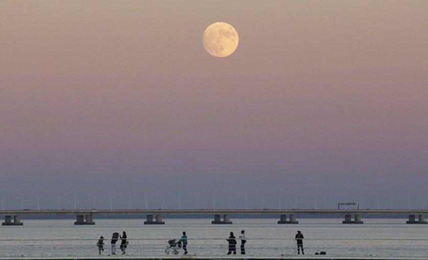Луна над рекой Тежу в Лиссабоне, Португалия.