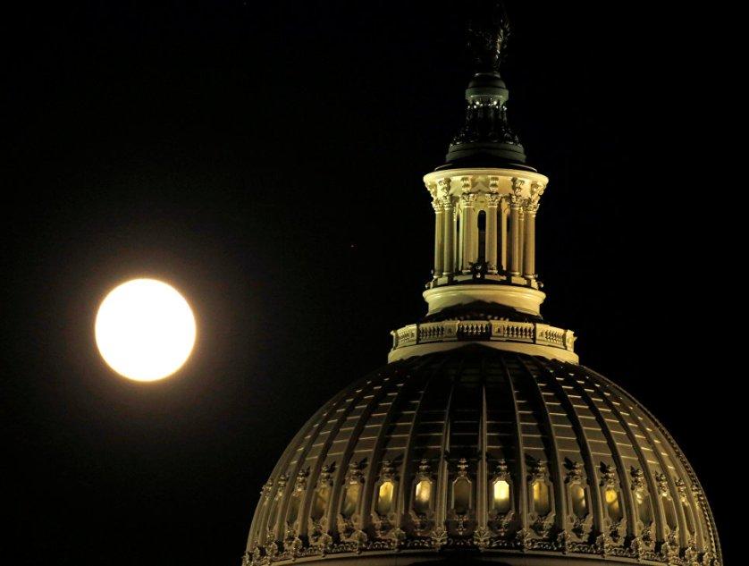 Луна поднимается над Капитолием накануне суперлуния в Вашингтоне, США.