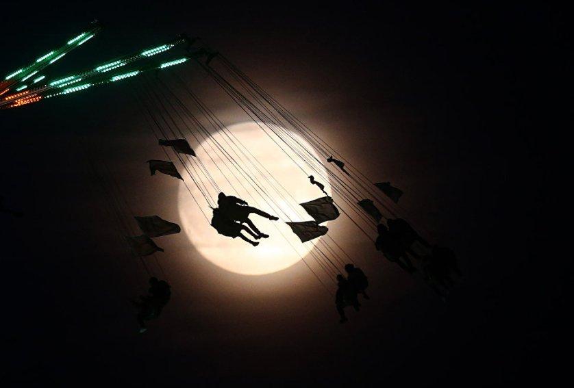 Люди катаются на каруселях на фоне луны в Лондоне, Великобритания.