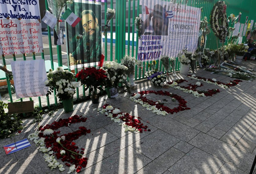 """Свежие букеты цветов и плакат с надписью на испанском """"Спасибо, Фидель!"""" появились утром в субботу у здания посольства Кубы в Мехико после известия о смерти Фиделя Кастро."""