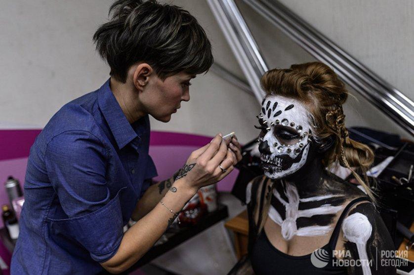 """Участница гримирует модель во время финала конкурса """"Лучший гримёр года""""."""