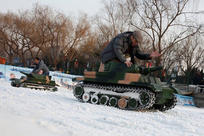 Люди катаются на электрических игрушечных танках в парке Таожаньтин в последний день китайского Нового года в Пекине.