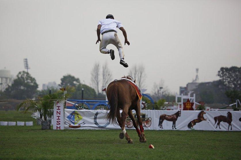 Солдат непальской армии демонстрирует навыки верховой езды во время ежегодного фестиваля лошадей в Катманду.