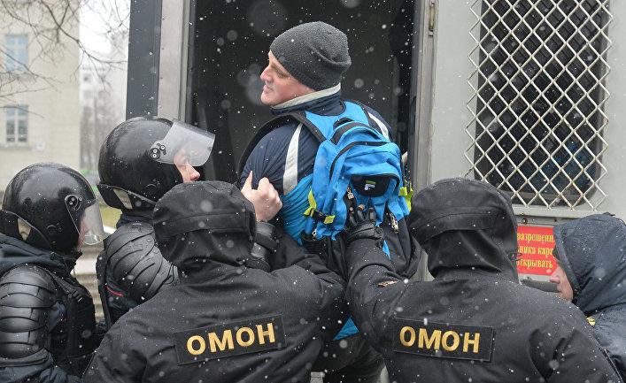 Сотрудники ОМОНа задерживают мужчину во время несанкционированной акции оппозиции в Минске.