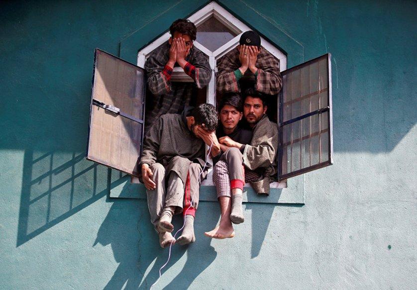 Люди наблюдают из окна мечети за похоронами командира боевиков, погибшего в перестрелке с индийской армией в Южном Кашмире, Индия.