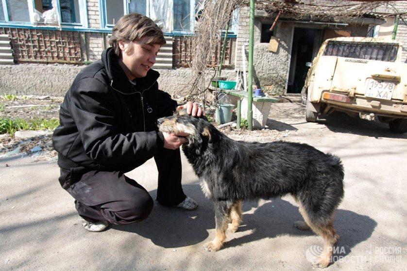 Местный житель с собакой на улице Привокзальной в прифронтовом поселке Донецк-Северный.
