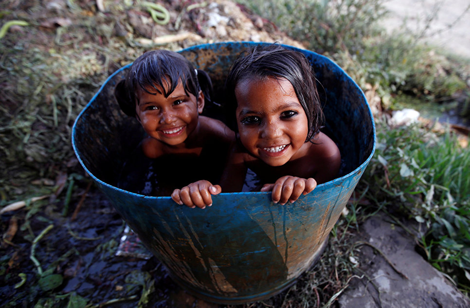 Девочки устроили себе ванну в старом барабане, Нью-Дели, Индия.