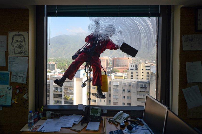 Работник моет окно офисного здания в Каракасе, Венесуэла.