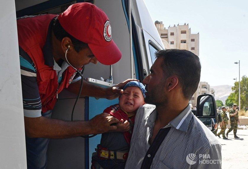 Представители Сирийского арабского красного полумесяца оказывают медицинскую помощь жителям Кабуна.
