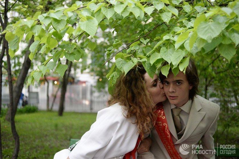 Выпускник с мамой во время последнего звонка в московской школе № 2123 имени Мигеля Эрнандеса.