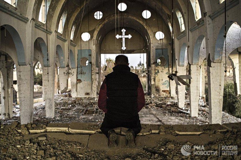 Житель одной из деревень провинции Эль-Хасаке молится в храме Святого Георгия, разрушенного боевиками ИГ(террористическая организация, запрещенная в России). Сирия, 08.12.2015.