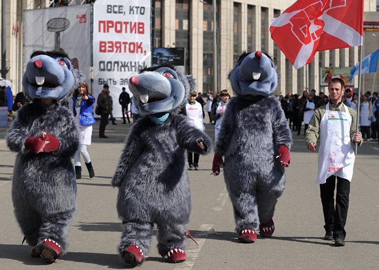 """Молодые люди в костюмах крыс, символизирующих коррупционеров, принимают участие в антикоррупционной акции """"Белые фартуки"""", которую проводят активисты молодежного движения """"Наши""""."""