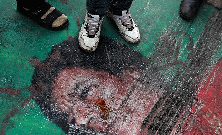 Лежащий на земле портрет Муамара Каддафи со следами протекторов автомобилей.