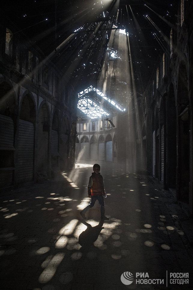 Дети играют в одном из зданий разрушенного района Хомса аль Хамидия.  Сирия, 12.12.2015.
