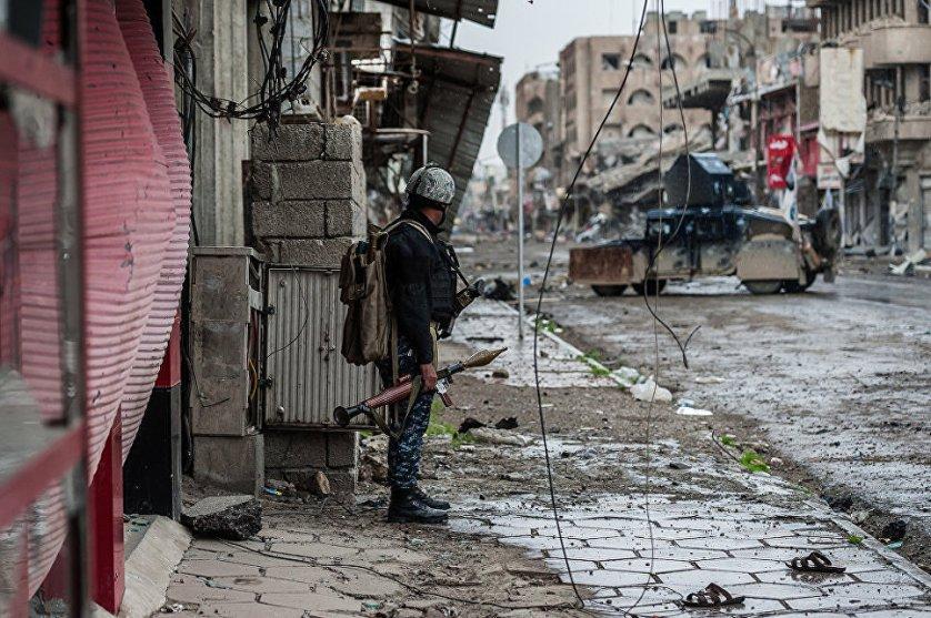 Боец федеральной полиции, вооруженный реактивным противотанковым гранатометом, осматривает позиции ИГИЛ* в районе боевых действий в зоне аэропорта.