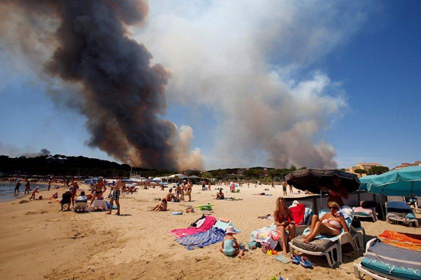 Дым от лесных пожаров над пляжем в Провансе, Франция.