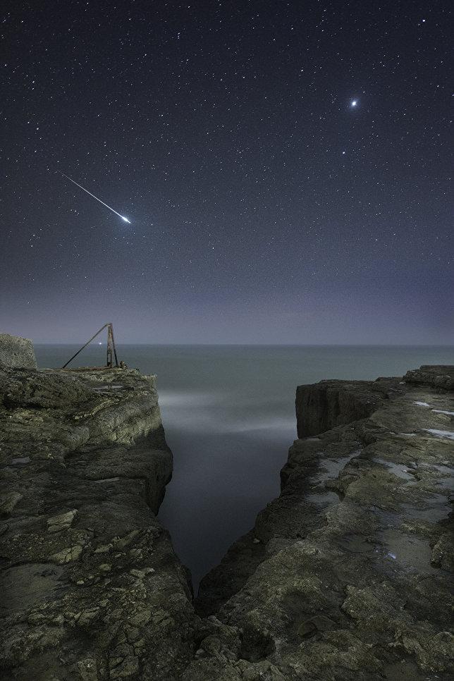 """Работа фотографа Rob Bowes """"Падающая звезда и Юпитер"""". Снимок был сделан над скалами в графстве Дорсет на острове Портленд. Фотография является наложением двух кадров: неба и горной породы."""