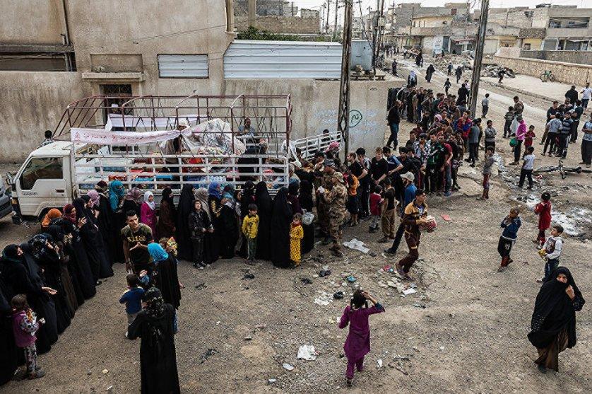 Мирные жители из района Мансор собрались для получения провизии от неправительственной организации, базирующейся в Восточном Мосуле.