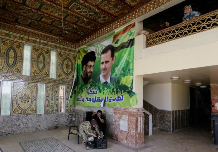 Сирийцы собрались в фойе поврежденного жилого дома к югу от Дамаска, на  стене  висит  плакат  с  портретами  президента Сирии Башара Асада  и Хасана  Насраллы, лидера  шиитского движения Хезболла в Ливане.