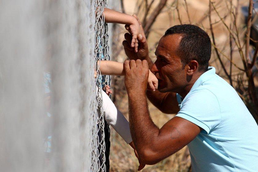 Сириец Аммар Хаммашо целует руки своих детей, прибывших в лагерь беженцев близ Никосии на Кипре.