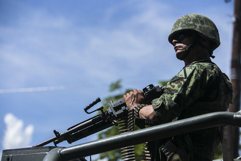 Солдат во время перевозки тел военных, убитых накануне в результате нападения, в Кульякане, Мексика