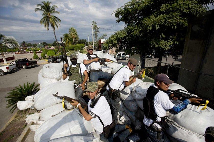 Вооруженные люди из Совета самообороны Мичоакана пытаются поймать предполагаемых членов Картеля тамплиеров в городе Нуэва Италия