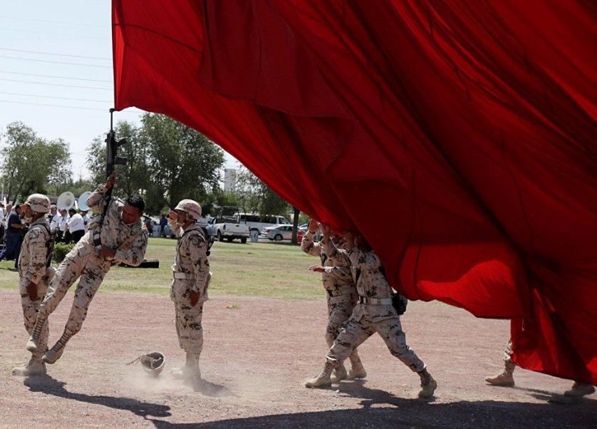 Солдат случайно зацепился винтовкой за национальный флаг во время подготовки к торжествам в честь 207-й годовщины независимости Мексики от Испании.