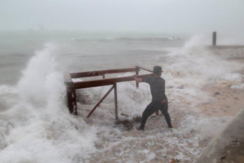 Мужчина пытается спасти стол, принадлежащий его ресторану, до того, как ураган Мария обрушится на Пунта-Кану, Доминиканская республика.