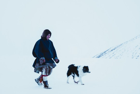 a nenets man in traditional clothing walks through the snow with his dog