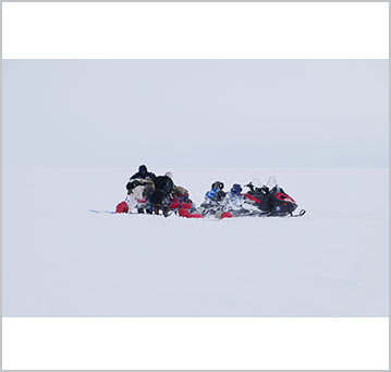 Vladimir stands next to the snowmobiles at the start of the expedition