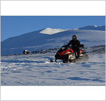Driving the snowmobiles on a crisp blue sky day in the arctic