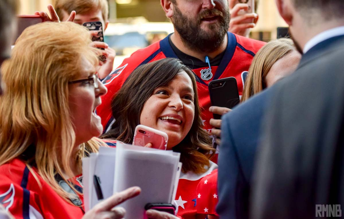 A Caps fan smiles as she meets one of the players