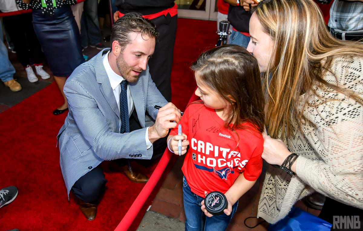 Brooks Orpik signs the back of a kid's shirt