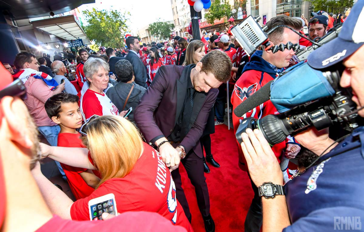 Evgeny Kuznetsov signs the back of a Kuzy shirsey