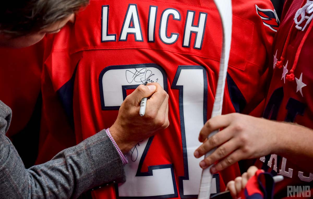 Oshie signs the back of a Brooks Laich jersey