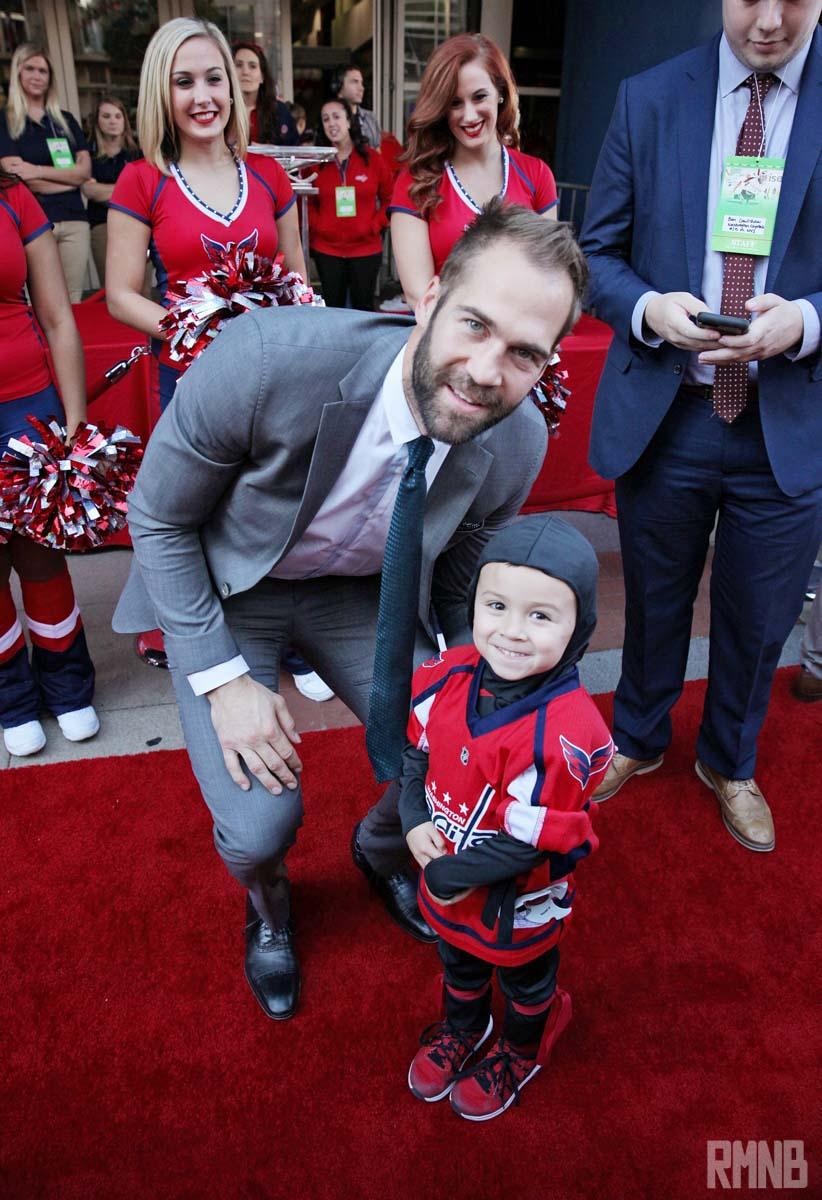 Daniel Winnik poses for a photo with a tiny fan