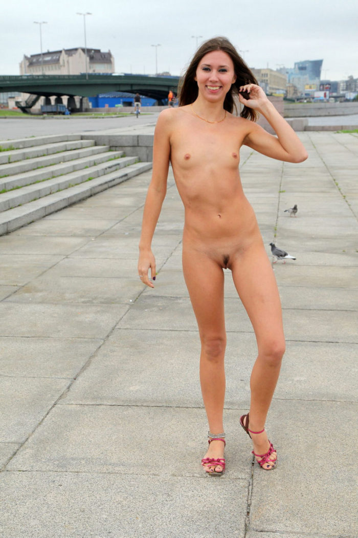 Cheerful babe with skinny body at public place