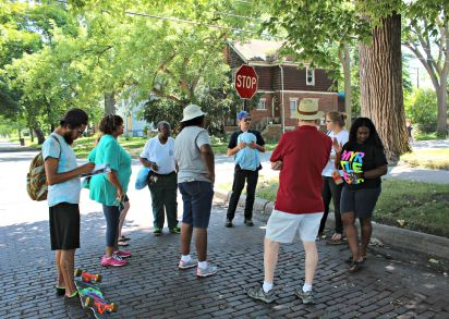 Members of the Lower Eastside Action Plan and Hope Community Development lead a neighborhood tour for Neighborhoods Day. The brick street we're standing on used to lead to the Detroit Driving Club, where Henry Ford raced an automobile that would become a Cadillac.