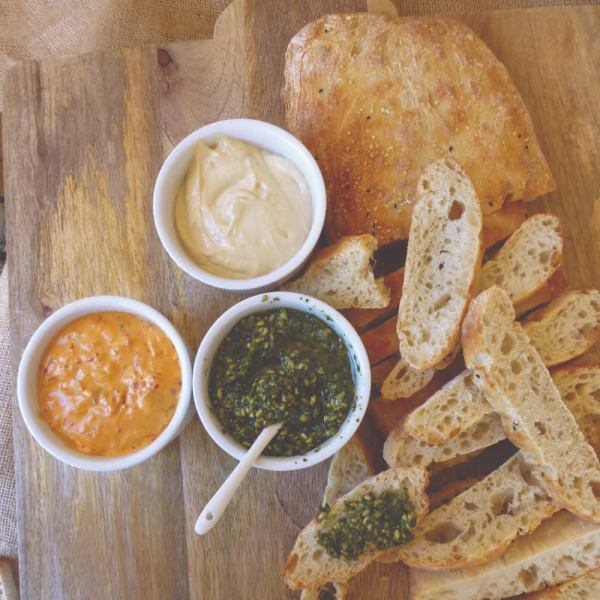 A wooden platter with sliced Turkish bread and three dips.