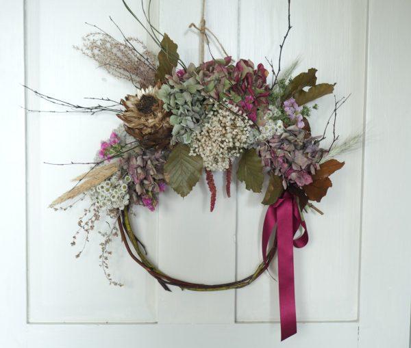 Wicker wreath with pink hydrangea, artichoke and birch