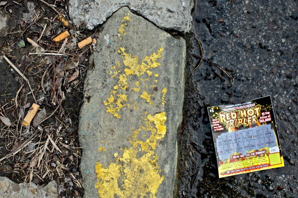 Losing lottery ticket discarded curbside. Peeling yellow paint on concrete.