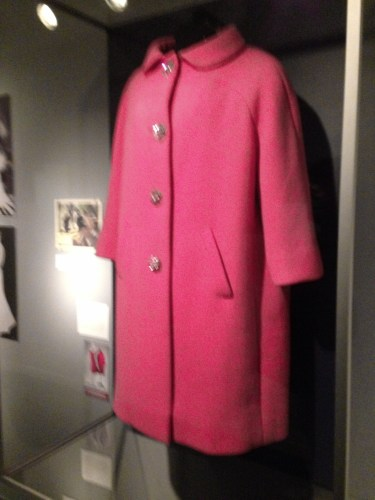 """A vivid pink wool coat by Norman Norell, worn by Bacall in the 1964 film Sex and the Single Girl, is on display."""