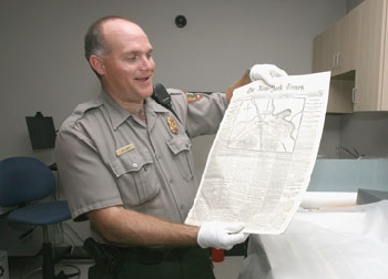 Ranger Jim Lewis displays Stones River Battlefield's rare copy of the New York Times coverage of the battle.