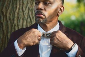 Man adjusting black skinny bow tie with botanical print