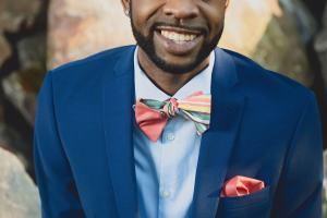 Smiling man wearing bow tie half pink and half multi stripe