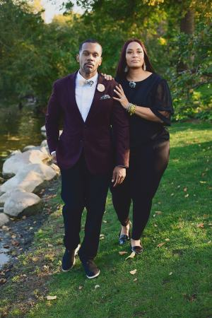 couple walking together. man wears black botanical print pocket square and woman wears matching flower pin