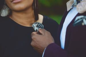 Man admires woman's flower pin while he wears matching pocket square