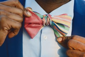 man holding edges of bow tie half pink and half multi color stripe