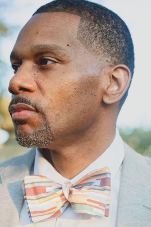 man wearing multi color stripe bow tie