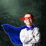 school boy wearing a superhero costume with blackboard behind him